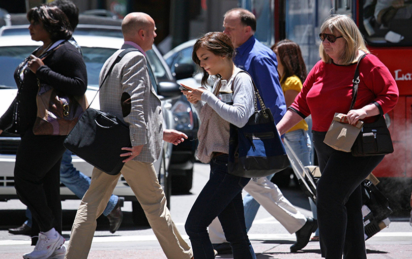 Peões atravessam a estrada a falar ao telefone, a enviar Mensagens e a ver vídeos